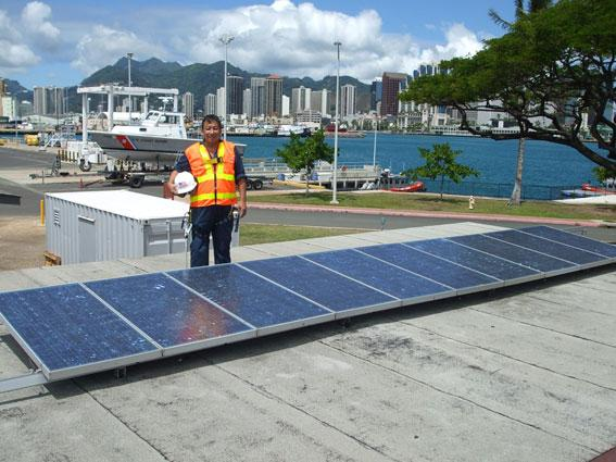 Lorrin Ching stands by the photovoltaic array