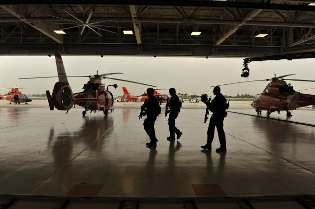 Three Coast Guardsmen preparing to board a Coast Guard helicopter.